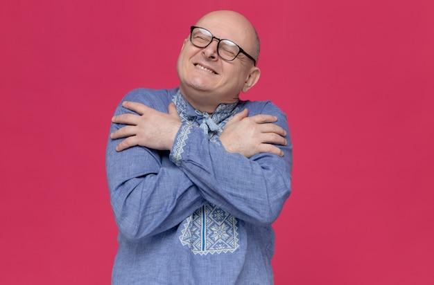 Erfreut erwachsener mann im blauen hemd mit brille, der sich selbst umarmt