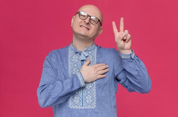 Erfreut erwachsener mann in blauem hemd mit brille, der die hand auf seine brust legt und das siegeszeichen gestikuliert