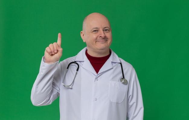 Erfreut erwachsener slawischer mann in arztuniform mit nach oben zeigendem stethoskop
