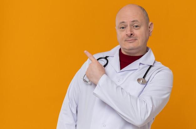 Erfreut erwachsener slawischer mann in arztuniform mit seitlichem stethoskop