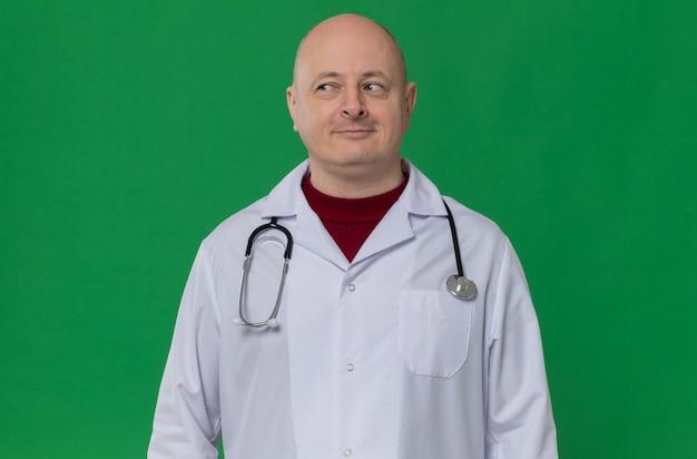 Erfreut erwachsener slawischer mann in arztuniform mit stethoskop auf der seite