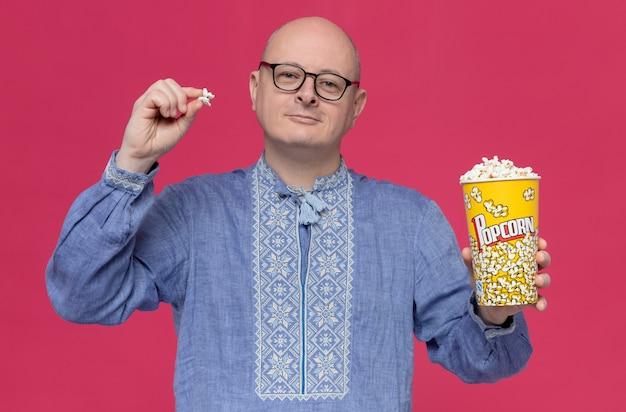 Erfreut erwachsener slawischer mann in blauem hemd mit optischer brille, der popcorn-eimer hält