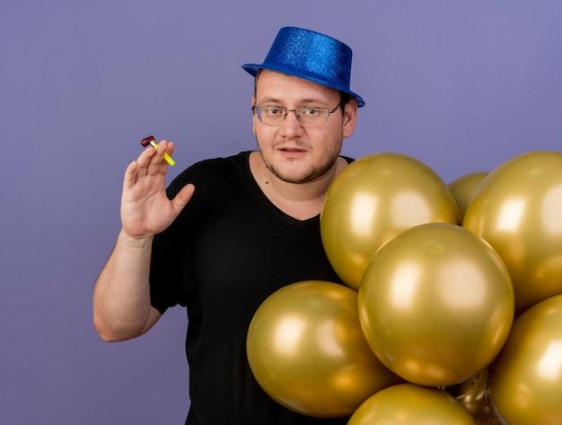 Erfreut erwachsener slawischer mann in optischer brille mit blauem partyhut steht mit heliumballons, die partypfeife halten holding