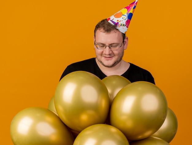 Erfreut erwachsener slawischer mann in optischer brille mit geburtstagsmütze steht mit heliumballons