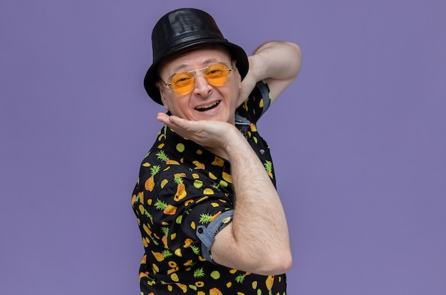 Erfreut erwachsener slawischer mann mit schwarzem hut mit sonnenbrille, der die hand auf sein kinn legt und nach vorne schaut
