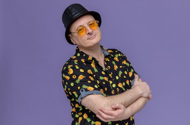 Erfreut erwachsener slawischer mann mit schwarzem hut mit sonnenbrille, der mit verschränkten armen steht
