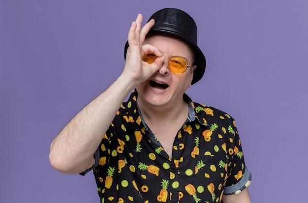 Erfreut erwachsener slawischer mann mit schwarzem hut und sonnenbrille, der durch seine finger nach vorne schaut