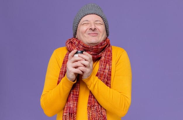 Erfreut erwachsener slawischer mann mit wintermütze und schal um den hals, der pappbecher hält