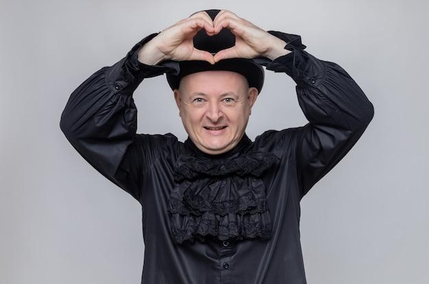 Erfreut erwachsener slawischer mann mit zylinder und im schwarzen gothic-hemd, der herzzeichen gestikuliert