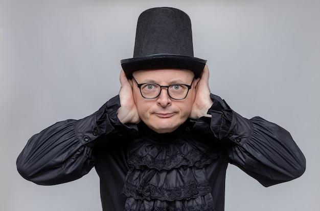 Erfreut erwachsener slawischer mann mit zylinder und optischer brille in schwarzem gothic-hemd, der die hände auf die ohren legt und nach vorne schaut