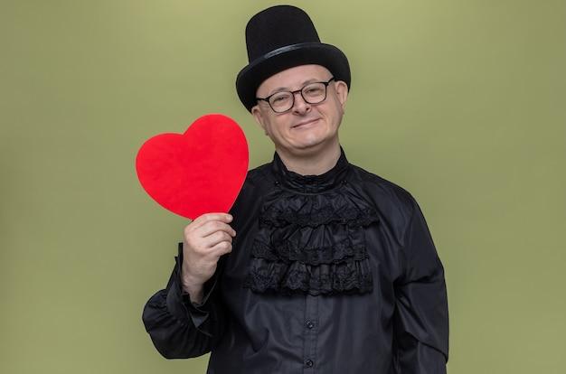 Erfreut erwachsener slawischer mann mit zylinder und optischer brille in schwarzem gothic-hemd, der rote herzform hält und nach vorne schaut