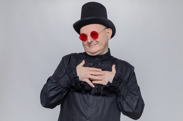 Erfreut erwachsener slawischer mann mit zylinder und sonnenbrille in schwarzem gothic-hemd, der die hände auf seine brust legt
