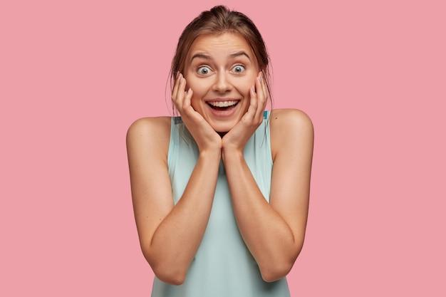 Erfreut fröhlich aufgeregte junge frau lächelt breit, hält die hände auf den wangen, zufrieden mit guten nachrichten, modelle gegen rosa wand, kann nicht an etwas wunderbares glauben, trägt freizeitkleidung