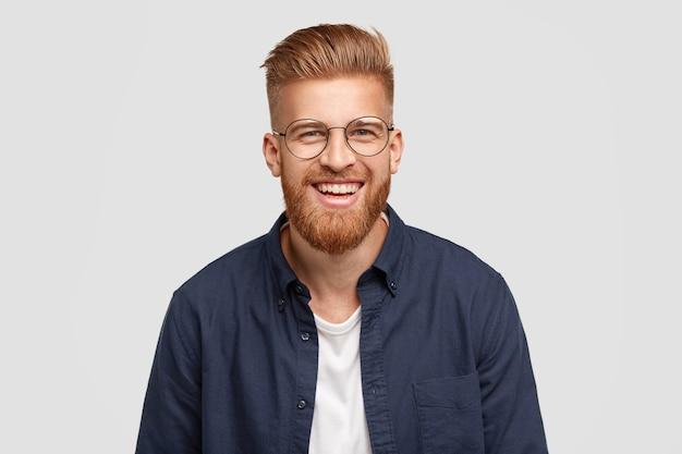 Erfreut fröhlicher rothaariger mann mit angenehmem lächeln