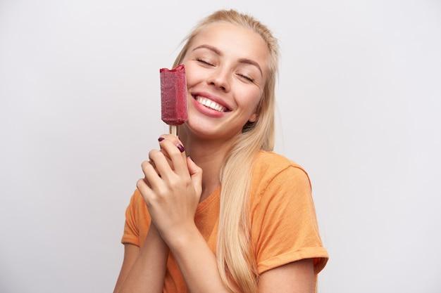 Erfreut gut aussehende hübsche junge blonde frau in freizeitkleidung hält eis am stiel und lächelt aufrichtig mit geschlossenen augen, vor weißem hintergrund stehend