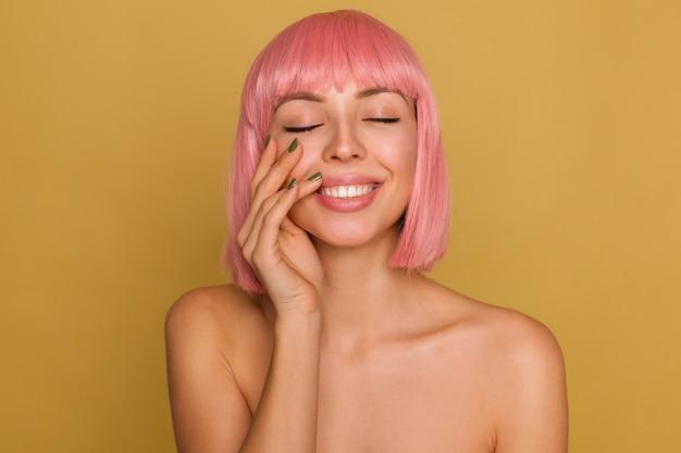 Erfreut gut aussehende junge pinkhaarige frau mit natürlichem make-up berührt sanft ihr gesicht mit erhobener hand und lächelt positiv, während sie über senfwand posiert