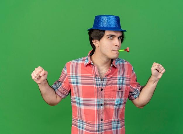 Erfreut gut aussehender kaukasischer mann mit blauem partyhut hält fäuste bläst partypfeife