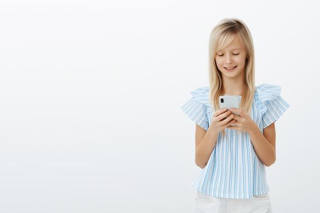 Erfreut gut aussehendes kleines weibliches kind mit blondem haar in blauer bluse, hält smartphone und lächelt auf bildschirm, während nachrichten oder lustiges spiel spielen