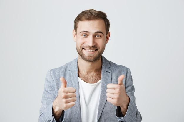 Erfreut, gutaussehender männlicher kunde zeigt zustimmend daumen hoch