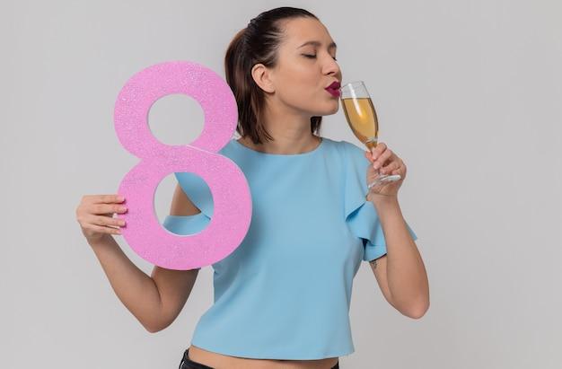 Erfreut hübsche junge frau, die rosa nummer acht hält und ein glas champagner trinkt