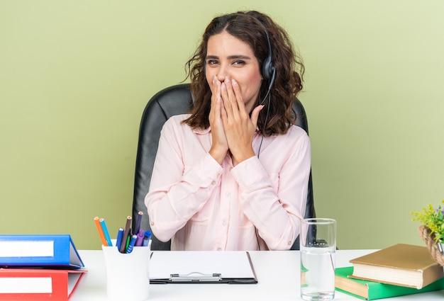 Erfreut hübsche kaukasische callcenter-betreiberin auf kopfhörern, die am schreibtisch mit bürowerkzeugen sitzen, die sich die hände auf den mund legen