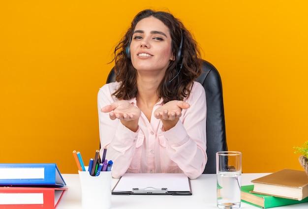 Erfreut hübsche kaukasische callcenter-betreiberin auf kopfhörern, die am schreibtisch mit bürowerkzeugen sitzen und die hände offen halten