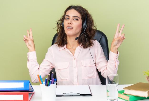 Erfreut hübsche kaukasische callcenter-betreiberin auf kopfhörern, die am schreibtisch mit bürowerkzeugen sitzen und siegeszeichen gestikulieren