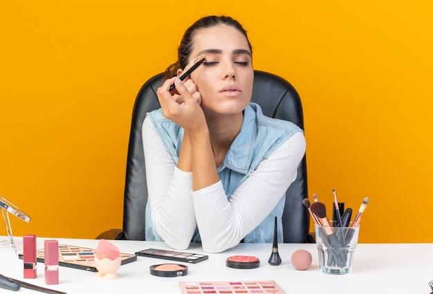 Erfreut hübsche kaukasische frau, die am tisch mit make-up-tools sitzt, die eyeliner auftragen