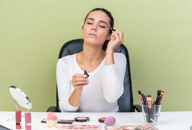 Erfreut hübsche kaukasische frau, die am tisch mit make-up-tools sitzt, die eyeliner einzeln auf olivgrüner wand mit kopienraum aufträgt