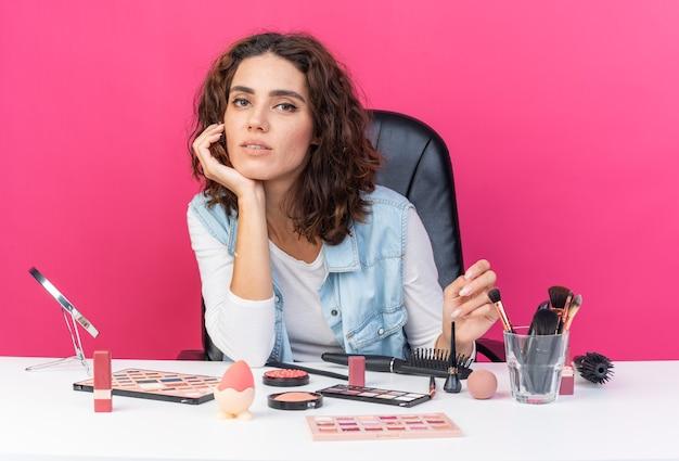 Erfreut hübsche kaukasische frau, die am tisch mit make-up-tools sitzt, die hand auf das kinn legt und auf rosa wand mit kopienraum isoliert ist