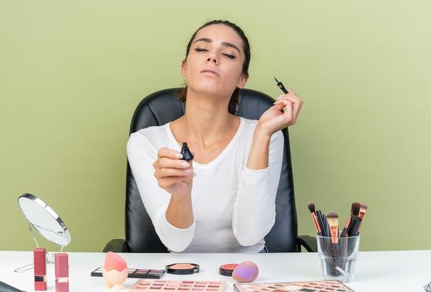 Erfreut hübsche kaukasische frau, die am tisch mit make-up-tools sitzt und eyeliner hält, isoliert auf olivgrüner wand mit kopierraum