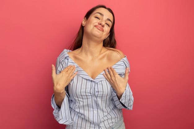 Erfreut hübsche kaukasische frau hände auf brust auf rosa