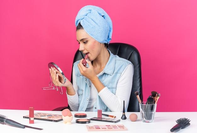Erfreut hübsche kaukasische frau mit eingewickeltem haar in handtuch, die am tisch sitzt und make-up-tools hält und den spiegel ansieht, der lippenstift aufträgt