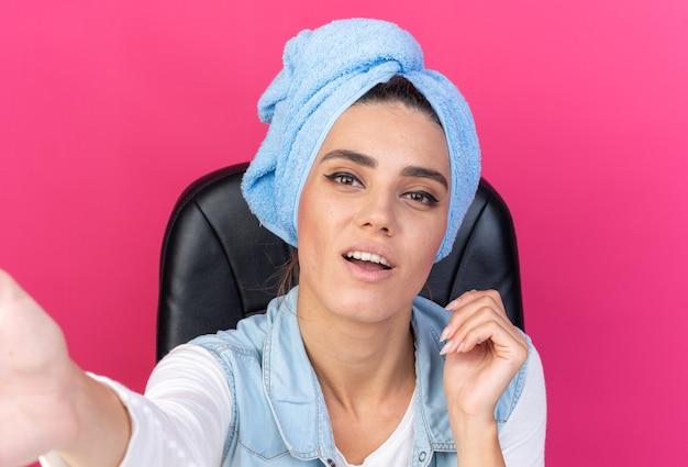 Erfreut hübsche kaukasische frau mit eingewickelten haaren im handtuch, die am tisch sitzt