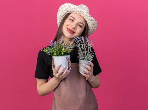 Erfreut hübsche kaukasische gärtnerin mit gartenhut, die blumentöpfe isoliert auf rosa wand mit kopienraum hält