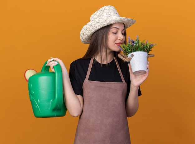 Erfreut hübsche kaukasische gärtnerin mit gartenhut, die gießkanne hält und blumen im blumentopf schnüffelt, isoliert auf orangefarbener wand mit kopierraum