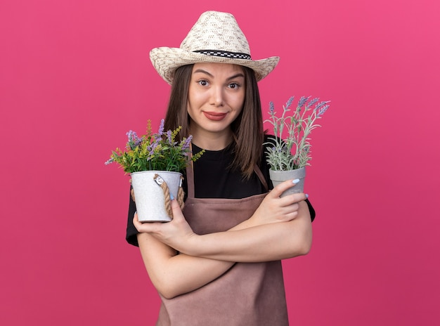 Erfreut hübsche kaukasische gärtnerin mit gartenhut steht mit verschränkten armen, die blumentöpfe isoliert auf rosa wand mit kopierraum halten