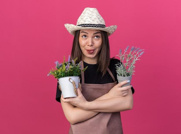 Erfreut hübsche kaukasische gärtnerin mit gartenhut streckt die zunge heraus und steht mit verschränkten armen, die blumentöpfe halten, die isoliert auf rosa wand mit kopienraum aufschauen