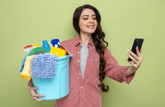 Erfreut hübsche kaukasische putzfrau, die reinigungsgeräte hält und auf das telefon schaut