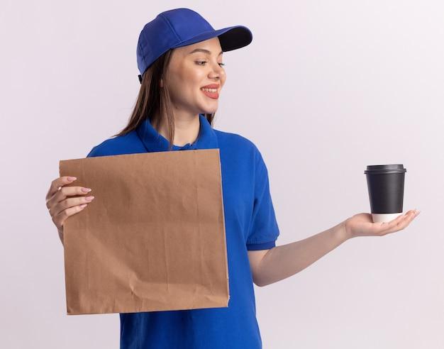 Erfreut hübsche lieferfrau in uniform hält papierpaket und schaut auf pappbecher isoliert auf weißer wand mit kopierraum