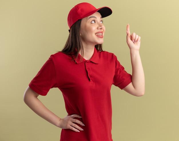 Erfreut hübsche lieferfrau in uniform sieht und zeigt nach oben