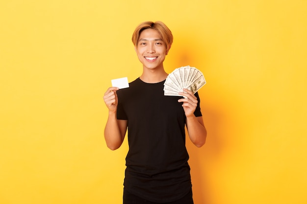 Erfreut hübscher asiatischer kerl, der geld und kreditkarte zeigt, glücklich lächelnd, stehende gelbe wand