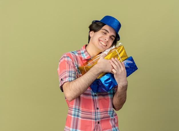Erfreut hübscher kaukasischer mann mit blauem partyhut hält geschenkboxen