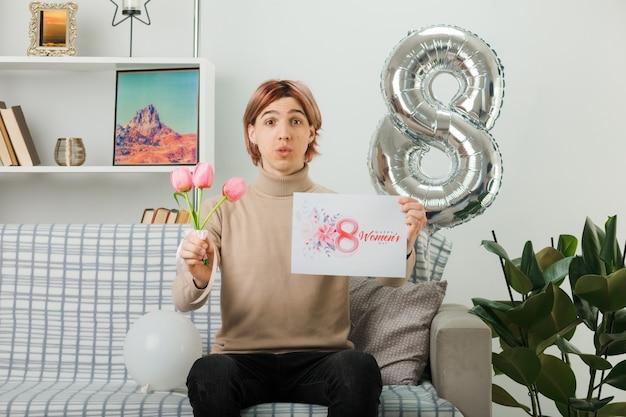 Erfreut hübscher kerl am glücklichen frauentag, der blumen mit grußkarte auf dem sofa im wohnzimmer hält Kostenlose Fotos