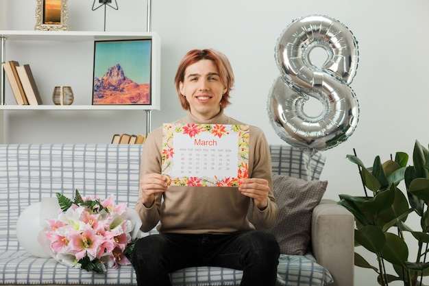 Erfreut hübscher kerl am glücklichen frauentag, der den kalender auf dem sofa im wohnzimmer hält