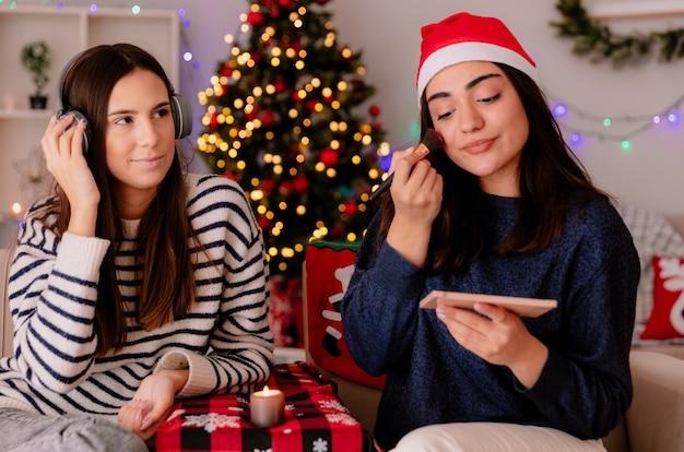 Erfreut hübsches junges mädchen mit weihnachtsmütze, das make-up macht und mit ihrer freundin auf kopfhörern auf einem sessel sitzt und die weihnachtszeit zu hause genießt