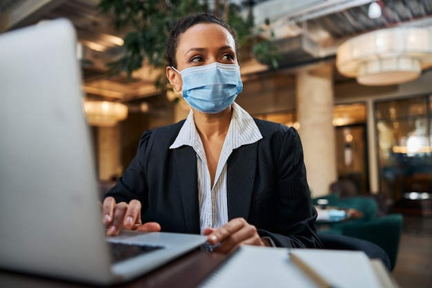 Erfreut internationale brünette, die maske im gesicht trägt, während sie sich an einem öffentlichen ort aufhält