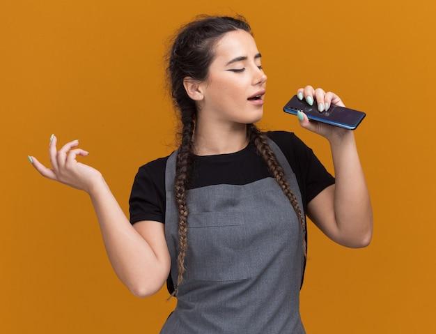 Erfreut junge friseurin in uniform mit telefon und gesang isoliert auf oranger wand