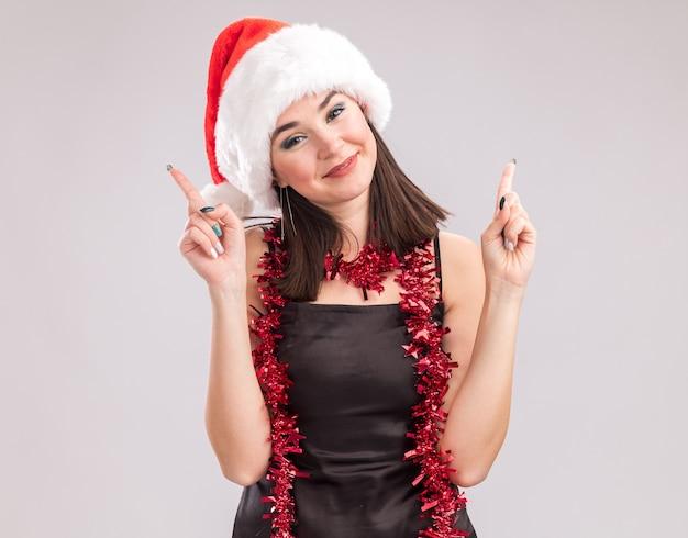 Erfreut junge hübsche kaukasische mädchen mit weihnachtsmütze und lametta girlande um den hals mit blick auf die kamera nach oben isoliert auf weißem hintergrund
