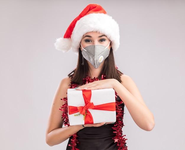 Erfreut junge hübsche kaukasische mädchen mit weihnachtsmütze und schutzmaske lametta girlande um den hals mit blick auf die kamera mit geschenkpaket isoliert auf weißem hintergrund